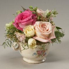 This is what I imagined as center pieces, except in a teapot instead of a teacup....also in her colors.....thoughts???