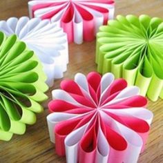 Cut the colored papers of red, white, green and even gold or silver if you have it into one inch strips about six inches long. Glue the ends together to form a circle. Let the glue from all the circles dry. Once all the circles are dry stack 9 circles on top of each other without flattening the ends. Place a staple in the center of the grouping and pull the halves slightly over to form a circle of loops. You now have a paper creation that resembles the famous Christmas ribbon candy