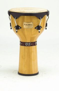"""Tycoon Percussion 12 Inch Artist Series Djembe - Natural Finish by Tycoon Percussion. $199.00. Tycoon Percussion's Artist Series Djembe is ideal for the gigging percussionist.  Constructed of carefully selected aged Siam Oak, super high gloss lacquer finishing protects the drum and looks great on stage.    Featuring high quality 12"""" goat skin heads, these drums cut through the mix on stage or in drum circles with ease.  Available in seven beautiful finish options, they are ligh..."""