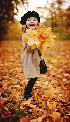 Russian child model Anna Pavaga. Anna with her arms full of leaves.