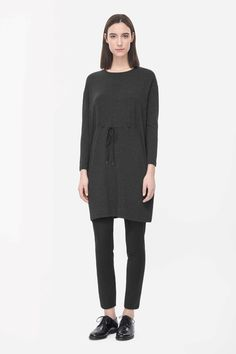 Made from soft and comfortable jersey with a melange quality, this dress has a drawstring tie fastening across the waist. A pull-on style, it is a loose, relaxed fit with a round neckline, long sleeves and neat stitched edges.