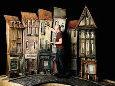 Art director Curt Enderle adjusting some of the buildings of Cheesebridge on the movie set for the movie The Boxtrolls.   Photo credit: photo by Jose Mandojana via wired.com