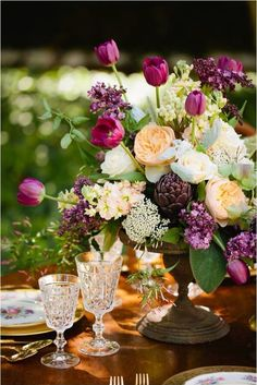 Elegant centerpiece with mix of color and flowers.  Lilac,  Tulips,  Stock,  Roses Queen Anne's lace,  ..+