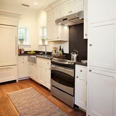 Though located in a tight space, this galley kitchen is highly effective; space is maximized with high cabinets and multiple drawers. The all-white color scheme and bright windows provide a sense of openness, and the cabinet-front refrigerator seamlessly blends with the rest of the cabinets. Honed black granite countertops and a matching stove backsplash provide contrast within the space.
