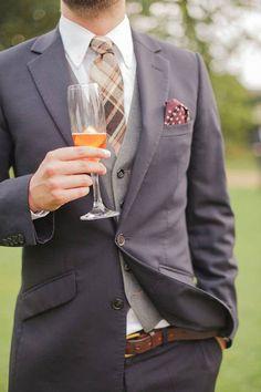 groom in navy suit, gray wool vest, and brown plaid tie