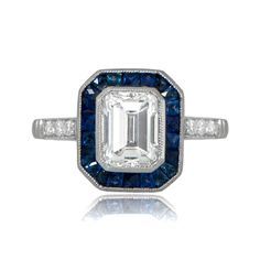 A beautiful Art Deco inspired engagement ring, adorned with a halo of sapphire around a stunning emerald cut diamond. Diamonds along the shoulders.