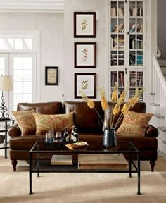 Striking and grounded, this room's basic strategy really works – the sofa and coffee table combination is given a confident twist with materials and form. The rectangular shape of the glass and wrought-iron coffee table is repeated in the framed wall art. A leather sofa stained a rich cognac invigorates the crisp white walls and acts as an inviting focal point for the entire space.