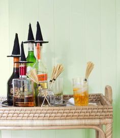 """Top your liquor bottles with witchy toppers. Step 1: Cut a 21/2"""" circle from black card stock. Glue paper circle between two pieces of black burlap. Trim burlap in shape of circle. Step 2: Roll another piece of burlap into a 3""""H cone shape and hot-glue edge to secure. Hot-glue cone to circle, then glue a piece of white twine around the base of the cone. Glue hat to bottle cork. Repeat to make additional hats. Let Halloween party guests get swept away by these adorable drink stirrers. Step 1…"""