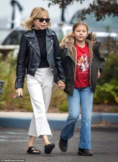 Mother-daughter style: While Michelle was clad in leather jacket, turtleneck and flaring trousers, Matilda opted for a faux fur-lined jacket, graphic-print T-shirt and jeans