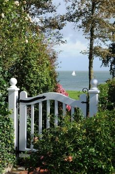 [This gate really invites you to slip through it. The gate and the plantings frame the view of the water in the most charming way, and the gate itself is a work of art.] Gate to the beach. Cottages By The Sea, Beach Cottages, Nantucket, Fence Gate, Fences, Picket Gate, Garden Cottage, Seaside Garden, Gate Design