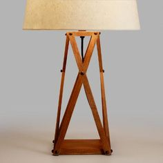 Featuring an architectural crisscross design, our industrial-style table lamp is crafted of wood in a washed finish and accented with dark metal rivets. Combine this mixed-material lamp base with any of our table lamp shades.