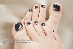 Navy blue pedicure with gold and white dot splash.