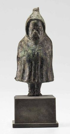 A GREEK BRONZE PAPPOSILENOS  HELLENISTIC PERIOD, CIRCA 1ST CENTURY B.C.  Solid cast, standing with his sandalled feet together, his arms resting on his bulging belly beneath his enveloping hooded cloak, with a frontal vertical seam along its length, undulating vertical folds falling below his arms, the hood with a conical projection in back, his face with a bald pate, bulging brows, articulated eyes, a rounded pug nose and a full mustache overlapping his pointed beard