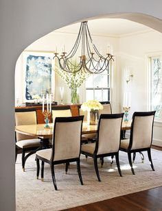 Understated elegance is the name of the game in the dining room with its bare windows and a graceful chandelier. - Traditional Home ®/ Photo: Werner Straube / Design: Julio Quiñones
