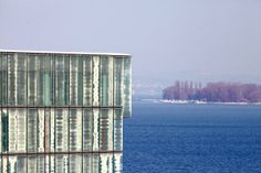 The sophisticated, multi-layered glass façade of Annette Gigon and Mike Guyer's Würth House in Rorschach, Switzerland, appears rippling; fitting for its setting on Lake Constance. Gigon Guyer, Laminated Glass, Glass Facades, Building Exterior, Safety Glass, Light Skin, Skyscraper, Coastal, Landscape