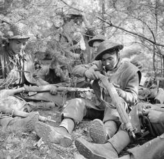 Men of 6th King's Own Scottish Borderers cleaning their rifles in a wood, 25 March 1945.