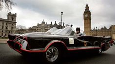 A man dressed as Batman drives the original Batmobile from the 1960's television series around Parliament Square in London.