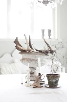 antler bits and wood make a rustic table setting  Teach painted metal candlesticks and pots