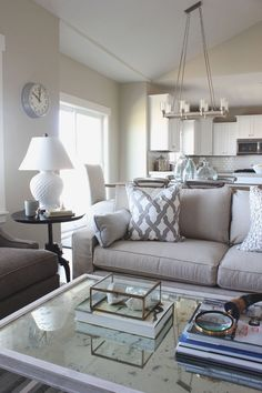 show n' tell - elkridge model home | alice lane home collection | neutral living room, white lamp, silver clock, black side table, antique mirror coffee table, gray chair, white kitchen, white subway tiles