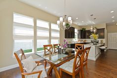 Light, bright and airy...just in time for spring! This beautiful breakfast room and kitchen from Bridgewater's elegant Clayton floor plan offers luxury, convenience and an exceptional layout. Can lights, a window wall with transoms, a custom island, beautiful two-tone cabinetry and unique lighting fixtures make an elegant living and entertaining space.   http://www.bridgewatercommunities.com