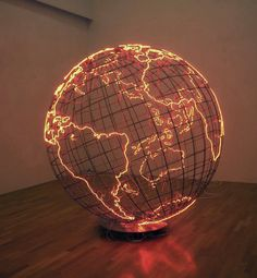 "In London and Berlin-based Palestinian artist Mona Hatoum's sculptural work titled ""Hot Spot"", we are presented with a massive cage-like metallic globe radiating a crimson glow. In terms of global politics and news, a ""hot spot"" generally refers to an area of conflict. Hatoum's piece highlights every land mass by outlining it in a neon red light that fills the room with an overwhelming scarlet hue. The structure seems to suggest that these neon contoured areas are the ""hot spots"" of the…"