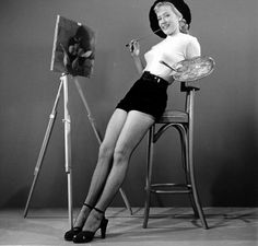 1940s (or would it be 50s?) pin-up photo of Betty Grable posing as a painter in a tight sweater and fishnets. - Source& copyright: Time Inc.