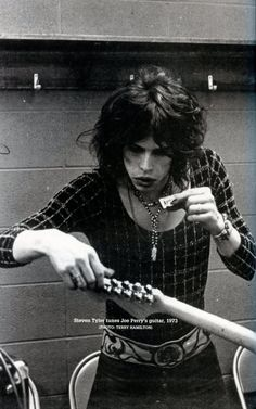 Steven Tyler tuning band's guitars with his harmonica  http://www.impactmerch.com/store/music/aerosmith.html