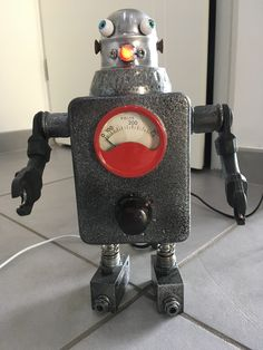 """Lamp design industrial robot chargeur de téléphone """"GUSTAVE""""   Je l'ai réalisé à partir de diverses pièces récupérées achetées ou recyclées.   Voltmètre ,raccords plomberie,pièces lampes ,voyant,yeux de poupées,ressorts,chargeur USB,connecteurs batterie etc.....   Dimensions environ 26cm  de hauteur et 18cm de large."""