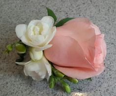 Coral rose boutonniere with white freesia.