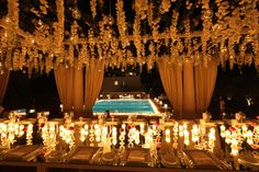 flowers dripping from above the tables is gently illuminated by the many candles is a gorgeous effect
