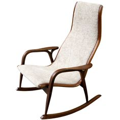 Yngve Ekstrom Rocking Chair  Sweden  1956  Ekstrom iconic design in a rare rocking chair version. Chair version seen quite often, rocker hard to find! Curved one piece design forms seat and back attaching to a walnut frame. Chair has been redone in a nubbly cream chenille.