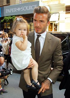 David Beckham is photographed with Harper, his little fashionista, after watching Victoria Beckham's fashion show