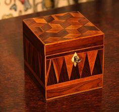 Antique Tea Caddy, Victorian Parquetry (English) cube shaped in rosewood and other woods.  Inlay of block shapes (tumbling blocks) gives a 3-dimensional effect.  Sides inlaid with geometric pattern of pennants.  Boxwood stringing around all edges.  Ivory keyhole escutcheon.