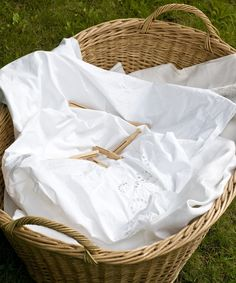 .An old laundry basket filled with fresh linens hung outside to dry