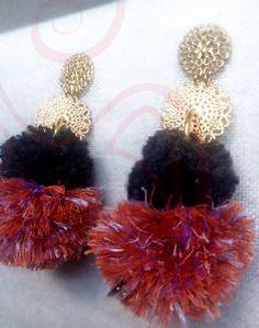 Orecchini pendenti interamente realizzati a mano: pon pon nero in 100% lino grezzo, pon pon rosso mattone in cotone e viscosa; perno a lobo in ottone. Leggerissimi