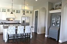great pattern on the bar stools and gorgeous grey and white kitchen on dark wood floors