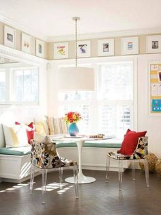 Framed prints above banquette, turquoise cushion with bright pillows