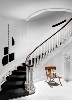 Adapting a timeless spiral staircase to modern taste... The mural in Ronald Bricke's stairwell is by Vesna Bricelj. The stoneware sculpture on the pedestal is by Halima Cassell.