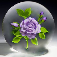 "Victor Trabucco paperweight - Purple rose blossom with three buds and having green leaves and stems. Signed on underside of one leaf with a ""VT"" signature cane and also signed in script ""Trabucco 1986, 2 3/4 'w x 2 3/4""t, 24.6oz - #0211"