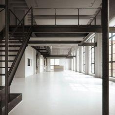 Monochrome Chicago loft apartment with white floors and black steel mezzanine