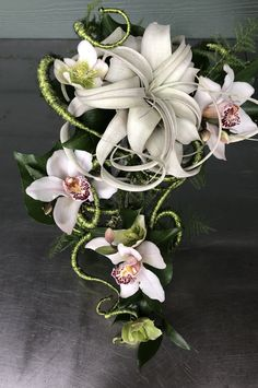 Cascade nouveau Cascade bridal bouquets are coming back. This is a next twist. So much more elegant with a contemporary feel. Tilandsia or air plants and orchids placed down a artesian holder will make everyone swoon.