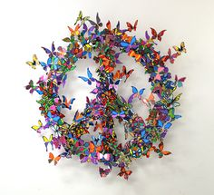 A David Kracov metal sculpture art work that uses colorfully painted butterflies to create a peace sign