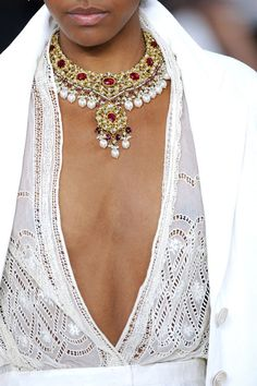 Gold and ruby necklace worn with a white lace dress