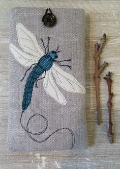 Machine embroidered dragonfly phone case, fully lined and finished with hoop and button, by Shropshire based designer Suzanne Bates.