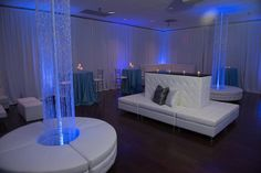 Lounge furniture banquette and doughnut ottoman with pipe and drape, blue uplighting and crystal columns for a cocktail style wedding reception at FOP89 in Maryland