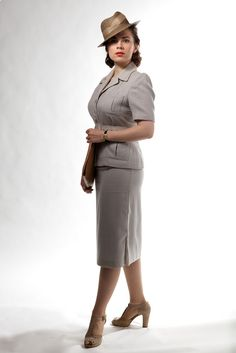 Women were in the workforce, and a suit dress was the official uniform. Note the hat set to the side and the peekaboo heels that served as feminine accents.