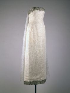a strapless evening dress in silver-spangled white tulle embroidered with rhinestones and trimmed with gray silk velvet. This dress was worn by Jacqueline Kennedy to the state dinner honoring President Felix Houphouet-Boigny of the Ivory Coast, the White House, Washington, DC, May 22, 1962