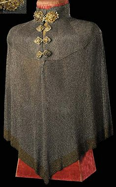 European (German) Bishop's Mantle, 16th c, over 100,000 very small riveted steel links with latten borders at the neck and hem, standing collar of semi-rigid mail extended downwards over the points of the shoulders, continued with slightly larger rings,  front opening extending to mid-chest level fastened by elaborate silver-gilt 'hook and eye' clasps, cast and chased with scrollwork and conventional foliage and with traces of coloured enamel, 31½in. (80cm.)