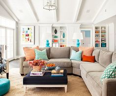 Everything in this room is neutral except for the accessories, which creates a vibrant look that is easily updated. Blue and orange accents in varying shades and saturations dot the room, making it a playful space.