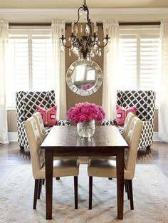 plantation shutters. white floor length drapes. geometric print chairs. bright pink large flowers.